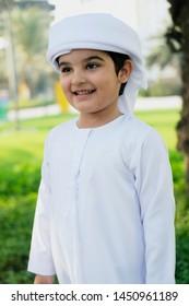 Smiling Muslim Kid looking away from the camera wearing traditional UAE kandura boys wear