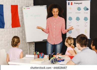 Smiling native speaker during French lesson with kids/Native speaker during French lesson/My name is ...