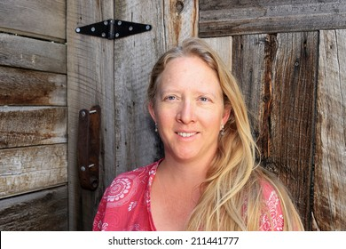 Smiling natural woman with a rustic barn wood background.