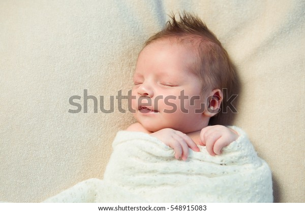 Un nouveau-né souriant aux cheveux mohawks dormant dans une couverture blanche.
