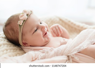 Smiling newborn baby. Photoshoot for the newborn. 7 days from birth. A portrait of a beautiful, seven day old, newborn baby girl