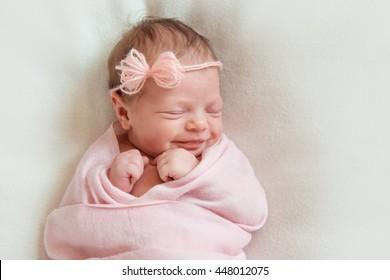 smiling newborn baby sleeping on white blanket