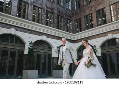 Smiling newlyweds walk along the boulevard, park, against the background of a brick building in the city, holding hands. Wedding portrait of a loving groom and a cute weightless woman.