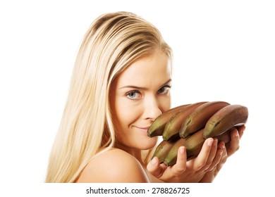 Nude girl eating banana can