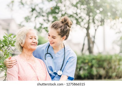 Smiling nurse caregiver with Asian elderly woman outdoor in the park