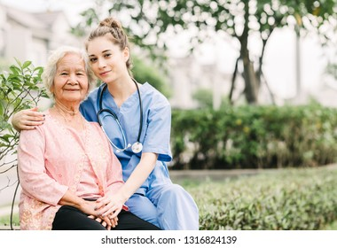 Smiling nurse caregiver embracing happy Asian elderly woman outdoor in the park