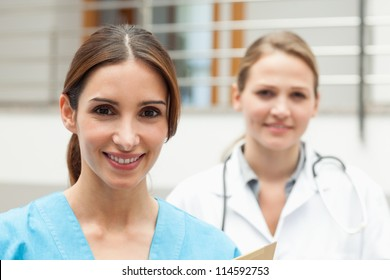Smiling nurse and doctor standing in a hospital reception