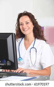 Smiling nurse in front of computer