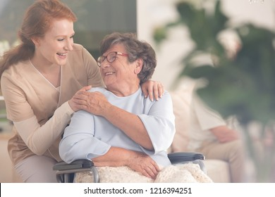 Smiling nurse helping happy senior woman in the wheelchair
