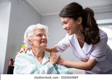 Smiling nurse and old woman patient at wheelchair at private nursing home