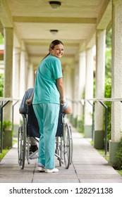 Smiling nurse pushing senior man in wheelchair in a nursing home
