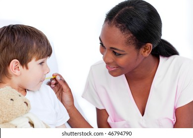 Smiling nurse taking little boy's temperature in a hospital