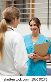 Smiling nurse talking to a doctor in a hospital reception