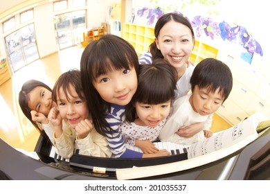 smiling nursery and children in front of the piano