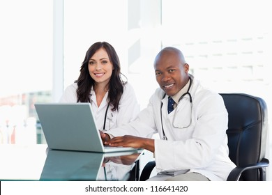 Smiling nurses seriously working while sitting at the desk in a bright room
