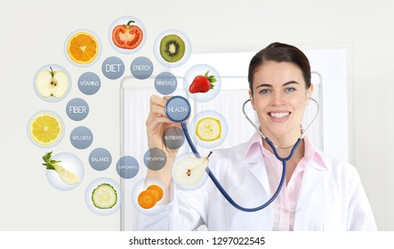 smiling nutritionist doctor with stethoscope pointing symbols fruits icons and medical texts isolated on white background, healthy food supplements diet plan concept
