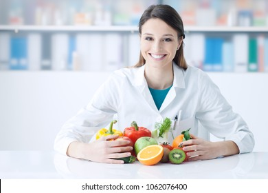 Smiling nutritionist in her office, she is holding healthy vegetables and fruits, healthcare and diet concept