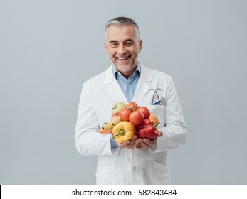 Smiling nutritionist holding fresh vegetables and fruit: healthcare and healthy vegetarian diet concept