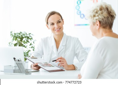 Smiling nutritionist showing a healthy diet plan to female patient with diabetes