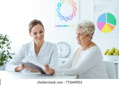 Smiling nutritionist showing personalized weight-loss diet plan to her senior patient
