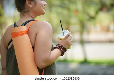 Smiling obese woman looking away and enjoying picturesque view at public park while refreshing herself with smoothie after productive fitness training