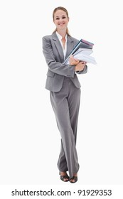 Smiling office employee with pile of paperwork against a white background