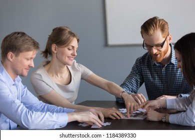 Smiling office team assembling puzzle together at meeting, creative happy people group connected in finding best business solution, successful teamwork, engaging in teambuilding help unity concept
