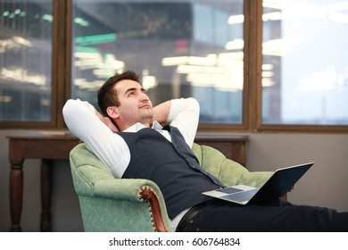 Smiling office worker relaxing in the armchair in officein Arlington city, Virginia.
