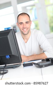 Smiling office worker sitting in front of desktop computer