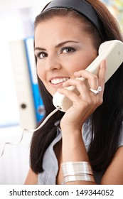 Smiling office worker talking on phone.