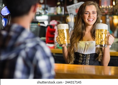 Smiling oktoberfest barmaid with beer at the bar