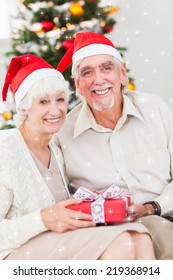 Smiling old couple swapping christmas gifts against twinkling stars