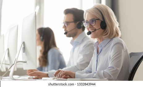 Smiling old female call center agent operator telemarketer in headset talking consulting online client at workplace, middle aged businesswoman using computer works in customer service support office
