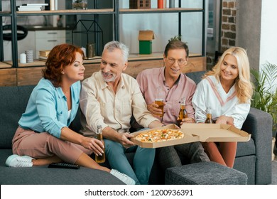 smiling old friends eating pizza and drinking beer while sitting on couch and spending time together at home