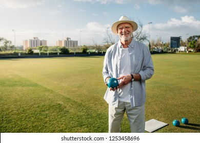 Smiling old man standing in a park with a boules in hand. Cheerful elderly man in hat standing in a play ground holding a boule.