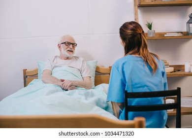 Smiling old patient in bed talking to nurse