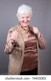 Smiling old woman at fight pose isolated against grey background