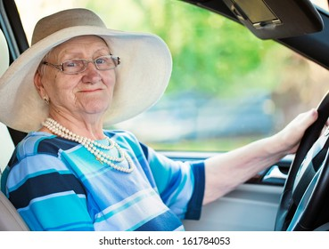 smiling old woman in glasses driving automobile