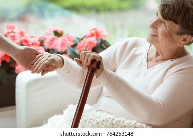 Smiling old woman holding hands of assistant while sitting on white sofa with walking cane