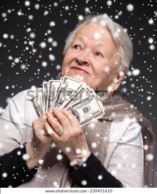 Smiling old woman holding money in hands. Christmas and holidays concept