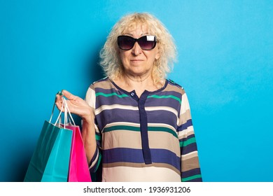 Smiling old woman holding shopping bags on blue background.
