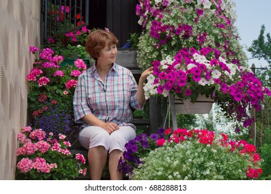 Smiling, old woman sits on the step near pots on a balcony in the garden. Floriculture is hobby Caucasian, elderly, mature mum, grandmother, senior cultivation ornamental plants. houseplants at summer
