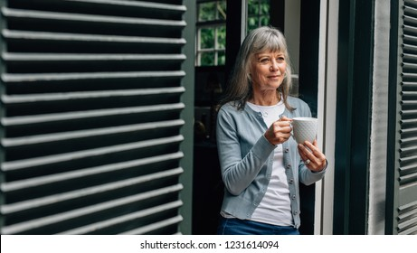 Smiling old woman standing at the door with a coffee cup in hand. Senior woman enjoying a cup of coffee standing at the door at home.
