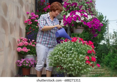 Smiling, old woman watering flowers in pots on a balcony in the garden. Floriculture is hobby. Caucasian, elderly, mature mum, grandmother, senior cultivation ornamental plants. houseplants at summer