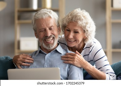 Smiling older couple looking at laptop screen together close up, mature woman and man making video call, reading good news on social network, chatting or shopping online, watching funny video