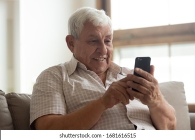 Smiling older man holding phone, using mobile device apps, looking at screen, happy mature male chatting online, texting, writing message, having fun with gadget, playing, sitting on couch