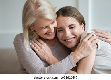 Smiling older mother and adult daughter hugging and laughing, family having fun together, young woman and mature mum enjoying tender moment, expressing love and support, two generations close up