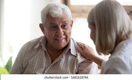 Smiling older patient attentively listening to caring mature female doctor close up, friendly middle-aged woman supporting, comforting elderly man, giving psychological help, healthcare concept