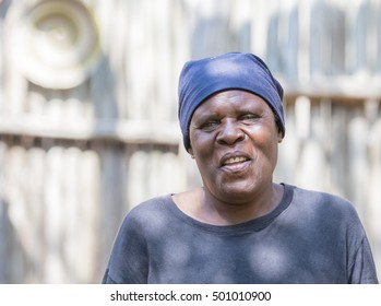 Smiling Older South African Woman Standing by Shed