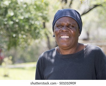 Smiling Older South African Woman with Yard in Background